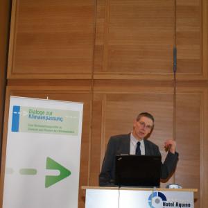Vortragender steht am Rednerpult und zeigt mit erhobenen Daumen hinter sich auf seine Präsentation, die im Hintergrund auf einer Leinwand zu sehen ist. Im Hintergrund steht der Veranstaltungsaufsteller Dialoge zur Klimaanpassung.