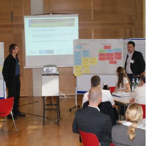 Zwei Teilnehmer präsentieren Ergebnisse an Moderationswänden. An den Moderationswänden hängen farbige Moderationskarten. Im Hintergrund sieht man noch eine Präsenation auf der Leinwand. Im Vordergrund sitzen Zuhörer an den Gruppenarbeitstischen.