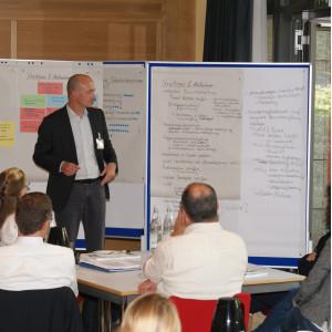 Vortragender steht vor Moderationswänden und präsentiert Ergebnisse. Im Vordergrund sitzen die Zuhörer am Gruppenarbeitstisch.