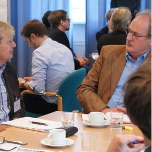 Teilnehmer sitzen am Gruppenarbeitstisch und sprechen miteinander. Im Hintergrund sitzen weitere Teilnehmer an Gruppenarbeitstischen.