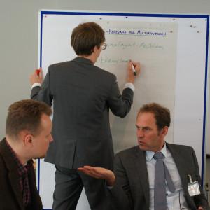 Teilnehmer schreibt auf Papier an Moderationswand. Im Vordergrund sitzen zwei Teilnehmer im Gespräch.