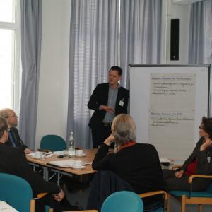 Teilnehmer sitzen am Gruppenarbeitstisch und hören Vortragenden zu. Der Vortragender steht neben einer Moderationswand.