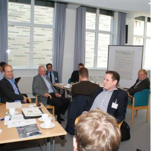 Teilnehmer sitzen an Gruppenarbeitstischen und lachen. Im Hintergrund steht eine Moderationswand vor der Fensterfront.