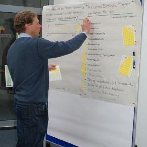 Teilnehmer steht vor Moderationswand und klebt gelbe Bewertungspunkte an zum Thema: Wie stark die Anpassung an den Klimawandel in der Institution verankert ist und mit welchen Themen der Teilnehmer befasst ist.