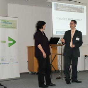 Ein Teilnehmer und eine Teilnehmerin befinden sich im Dialog miteinander. Im Hintergrund sieht man den offenen Laptop auf dem Rednerpult sowie den Veranstaltungsaufsteller und ein Herzliches Willkommen projiziert auf der weißen Wand.
