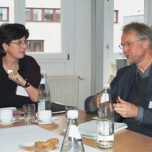 Zwei Teilnehmer sitzen am Gruppenarbeitstisch im Dialog miteinander vor einer hellen Fensterfront.