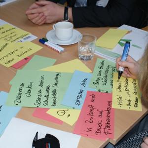 Farbige Moderationskarten liegen beschriftet auf dem Gruppenarbeitstisch. Eine Teilnehmerin beschreibt eine gelbe Moderationskarte zum Thema Naturschutz durch Anpassung