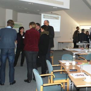 Teilnehmer stehen im Workshopraum in Grüppchen vor den Moderationswänden im Dialog miteinander.