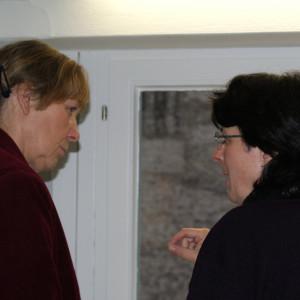 Zwei Teilnehmende stehen vor dem Fenster im Dialog miteinander.
