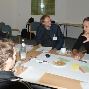 Teilnehmer sitzen am Gruppenarbeitstisch und hören einem anderen Teilnehmer zu.