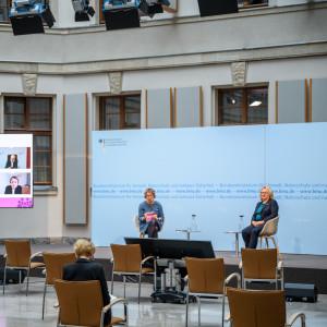 In dem hellen historischen Innenhof sitzen 2 Frauen auf Schalenstühlen auf dem Podium vor einem blauem Hintergrund. Links davon steht ein großer flacher Bildschirm, der die zugeschalteten Konferenzteilnehmenden zeigt. Vor dem Podium stehen leere Stühle. Auf einem Stuhl beugt sich eine Teilnehmerin über Ihre Unterlagen.