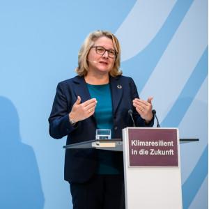 Die Umweltministerin steht am Rednerpult vor blauem Hintergrund und trägt gestikulierend vor.