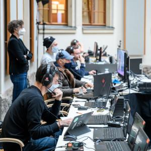 Die Technikerinnen und Techniker sitzen in einer langen Reihe und schauen konzentriert in die Laptops. Sie tragen Kopfhörer und Mund-/Nasenbedeckungen.