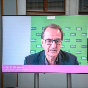 Auf einem flachen Bildschirm im hellen historischen Innenhof ist im Großformat zu sehen wie der Präsident des Umweltbundesamts einen Beitrag spricht.