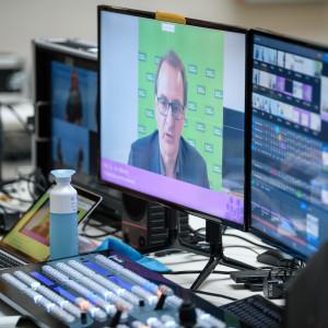 Der Blick geht auf den Technikerinnentisch Mischpult und Computerbildschirmen. Darauf sind die Teilnehmenden und verschiedenen Konferenzräume zu sehen.