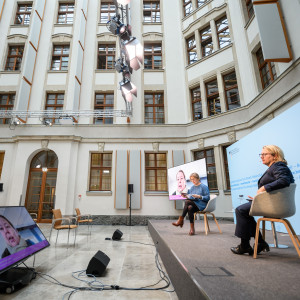 In einem historischen Innenhof mit natürlichen Licht sitzen zwei Frauen auf einem Podium auf hellen Schalenstühlen vor hellblauem Hintergrund und schauen vor sich runter auf einen flachen Bildschirm. Vor dem flachen Bildschirm stehen zwei schwarze Lautsprecher auf dem Boden. Im Hintergrund sitzt ein Mann auf einem Publikumsstuhl. Die Fassaden sind in einem freundlichen Hellgrau abgesetzt, die Fenster sind hölzern.