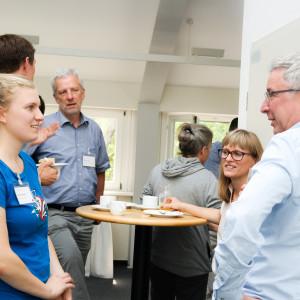 Kaffeepause während des Dialogs. Personen dabei stehen an Stehtischen und unterhalten sich. Der Raum ist in hellen Tönen gehalten. Im Vordergrund stehen eine Frau im blauen T-Shirt und ein Mann im hellfarbigen Hemd. Sie schauen sich an.