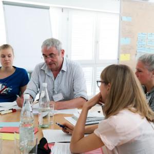 Planspiel: Teilnehmende sitzen an einem Gruppenarbeitstisch auf dem Getränke stehen und Papiere, farbige Moderationskarten liegen. Die Personen sehen nachdenklich aus.