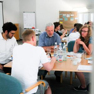 Planspiel: Teilnehmende sitzen an Gruppenarbeitstischen und denken nach. Im Vordergrund schreibt ein Teilnehmer im weissen T-Shirt etwas auf eine hellblaue Moderationskarte.