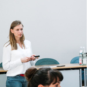 Vortragende steht vor einem Podiumtisch und hält einen Pointer in ihren Händen. Auf dem Podiumstisch stehen Gläser und Getränkeflaschen.