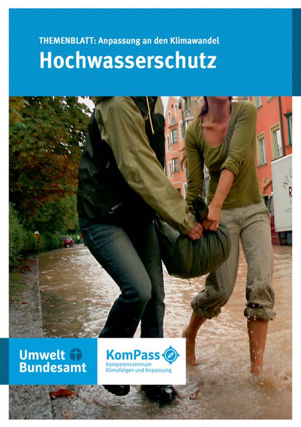 """Cover von """"Anpassung an den Klimawandel: Hochwasserschutz"""", Titelfoto: Zwei Frauen tragen gemeinsam einen Sandsack durch eine überflutete Straße"""