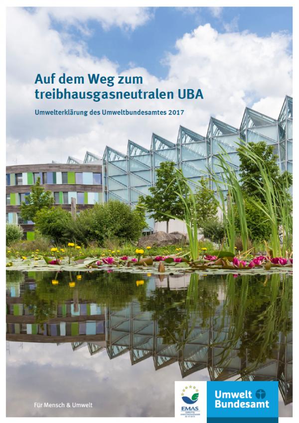 """Titelseite der Broschüre """"Auf dem Weg zum treibhausgasneutralen UBA: Umwelterklärung des Umweltbundesamtes 2017"""". Das Titelfoto zeigt einen Teich mit See- und Teichrosen, im Hintergrund das Gebäude des Umweltbundesamtes in Dessau mit moderner Holz-Glas-Fassade. Unten die Logos EMAS und Umweltbundesamt"""