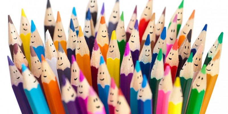 ein Bündel verschiedenfarbiger Buntstifte bei denen jeweils oben ein kleiner Smiley auf das Holz gemalt ist