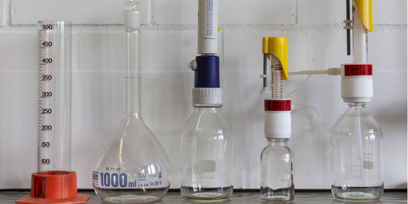 Das Bild zeigt verschiedene Laborutensilien wie z. B. einen Messbecher.