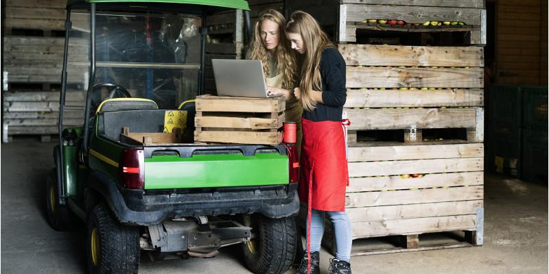 Auf dem Bild sind zwei Frauen auf einem Obstbauerhof zu sehen, die einen Laptop benutzen.