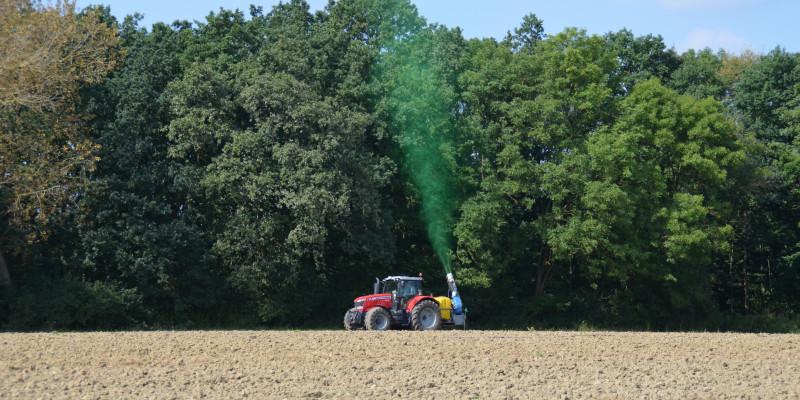 Das Bild zeigt einen Traktor an einem Waldrand, der mit Hilfe einer Sprühkanone Biozide in Richtung der Bäume ausbringt.