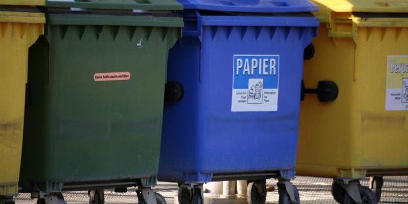 Müllcontainer in grün, blau und gelb für verschiedene Abfälle.