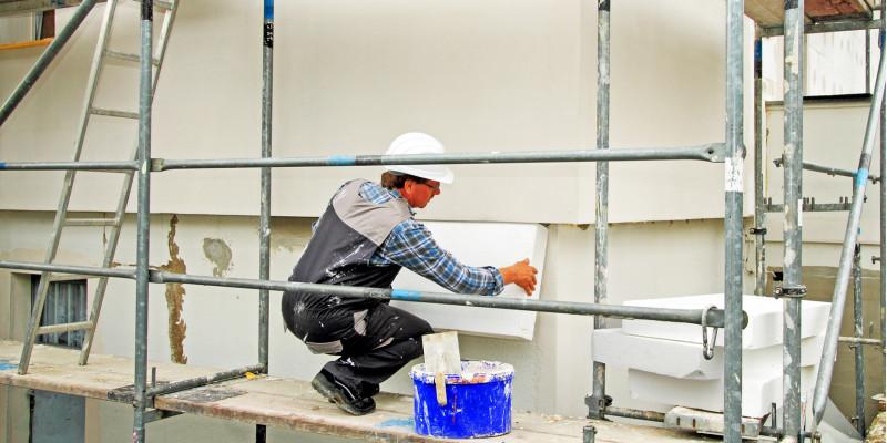 Ein Handwerker bringt Dämmung an einer Hausfassade an.