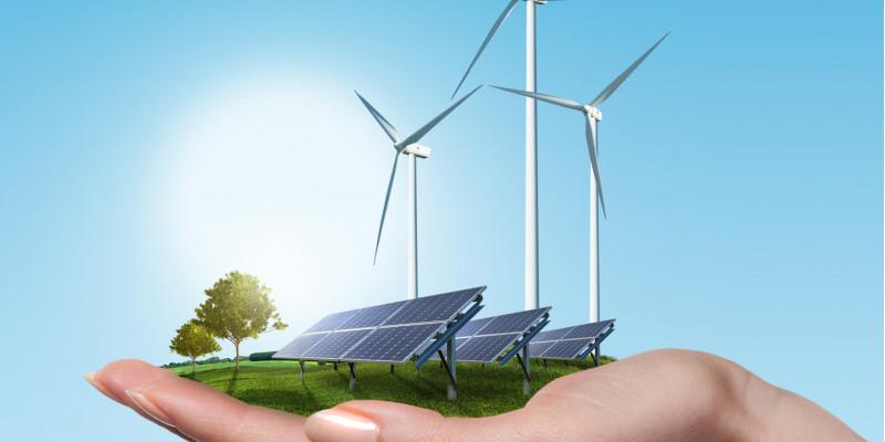 Hand hält Solarfeld und Windräder