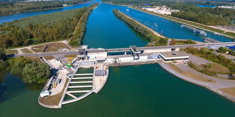 Foto: Das Wasserkraftwerk Iffezheim samt Staustufe am stark ausgebauten und begradigten Rhein. Im Vordergrund ist ein großer Fischpass zu sehen.