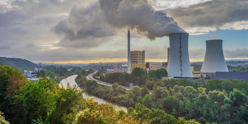 Foto: Zwei Kühltürme eines Wärmekraftwerks im unmittelbaren Umfeld eines Flusses. Aus einem Kühlturm tritt Wasserdampf aus.