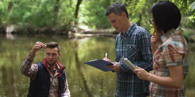 Foto: Drei Personen in Freizeitkleidung an einem Gewässer. Eine Person hält ein Glasgefäß mit einer Wasserprobe hoch, eine zweite Person macht Notizen auf einem Klemmbrett, die dritte Person hält ein Dokument in der Hand.