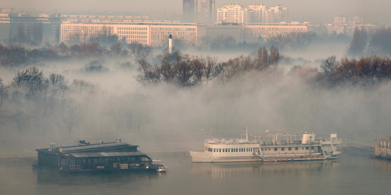 Foto: Nebel über einem Fluss und seinen Uferbereichen. Im Hintergrund sind die Häuser einer Stadt zu sehen.