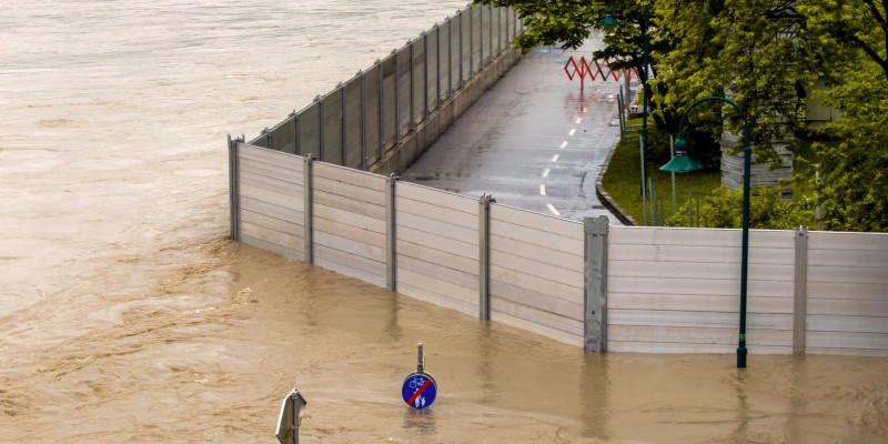 Foto: Eine mobile Hochwasserschutzwand trennt eine überflutete von einer trockenen Straße
