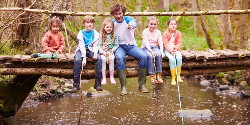 Foto: Mann sitzt mit fünf Kindern auf einer Holzbrücke, die über einen Waldbach führt. Der Mann zeigt auf etwas im Bach. Ein Kind hat einen Kescher in der Hand.