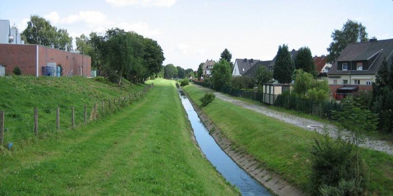 Foto: Der begradigte und mit Betonschalen ausgebaute Heerener Mühlbach in Kamener Wohnumfeld.
