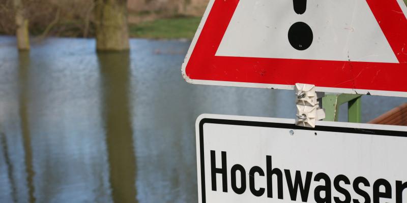 """Foto: Ein überschwemmtes Gebiet während eines Hochwasserereignisses. Im Vordergrund steht ein """"Achtung Hochwasser"""" Schild"""