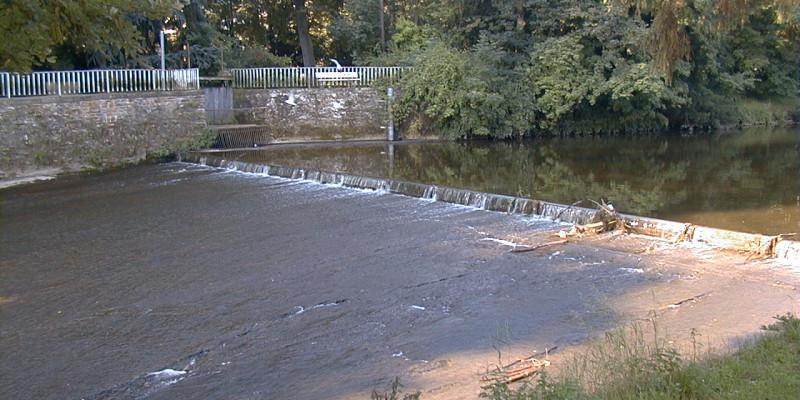 Foto: Seitlicher Blick auf Absturz mit darauffolgender, glatter Rampe. Oberhalb des Wehrs staut sich das Wasser.
