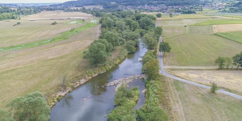 Luftbild der Fulda mit schräg zur Fließrichtung eingebrachten Steinen. Die dadurch abgelenkte Strömung hat bereits eine Erosion des Ufers bewirkt.
