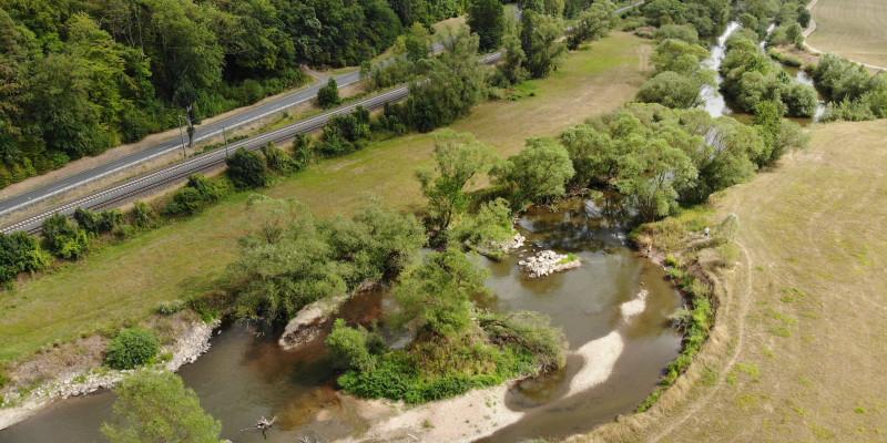 Luftbild der Fulda mit großzügiger Aufweitung und Kiesbänken, die teilweise mit Vegetation bedeckt sind. Links ist eine Straße zu erkennen, rechts grenzt Grünland an das Gewässer an.