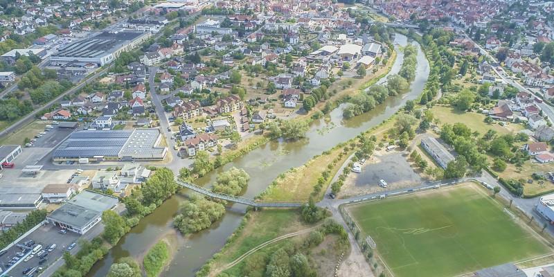 Luftbild auf breites Gewässerbett der Fulda in Rothenburg. Mehrere mit Vegetation bewachsene Inseln liegen im Gewässer. Im Gewässerumfeld liegen bebaute Flächen.