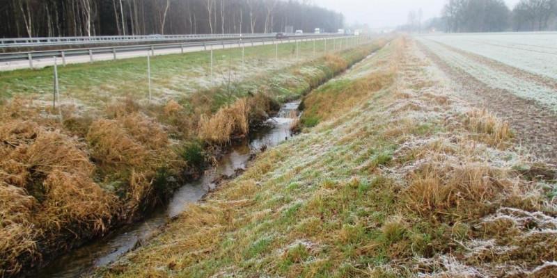 Foto: Der begradigte Schierenbach im V-Profil eingeengt zwischen Autobahn und Ackerfläche. Die Ufer sind bis auf kurze Gräser frei von Vegetation.