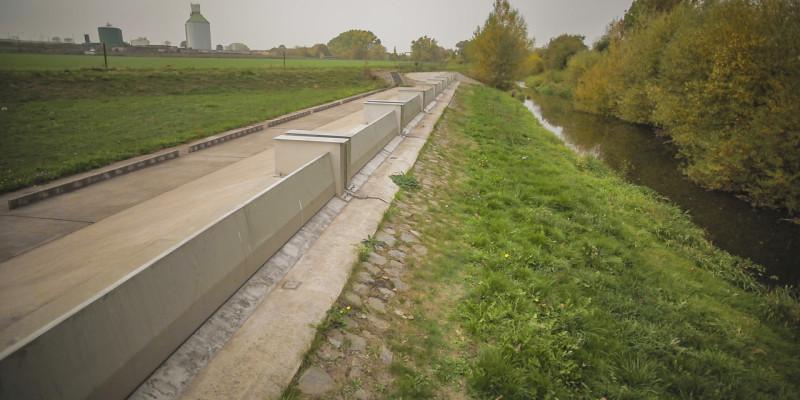 Foto: Das Klappenwehr aus Beton und Stahl auf einem Damm bei Sundhausen.