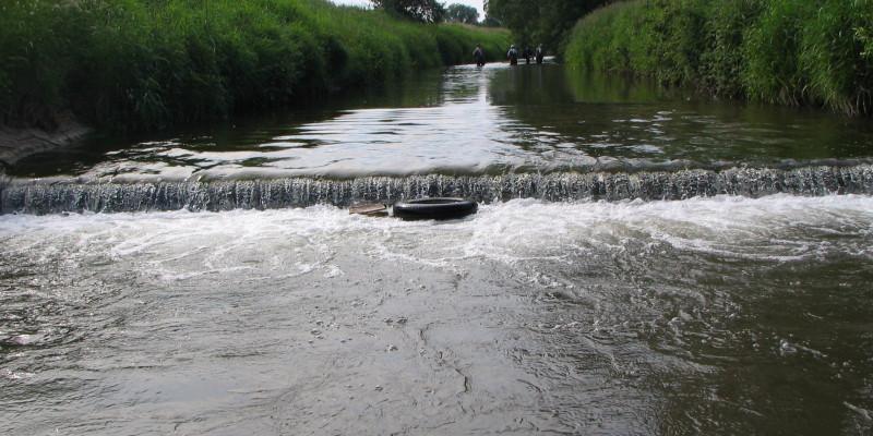 Foto: Eine Sohlschwelle in der Helme bei Nordhausen, an dem das Wasser mehrere Zentimeter hinabstürzt.