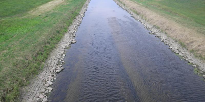 Foto: Ausgebauter Gewässerabschnitt der Murg bei Rastatt. Das Gewässer verläuft geradlinig durch die Landschaft. Der Böschungsfuß ist mit Steinen befestigt, die Ufer mit Gras bewachsen.