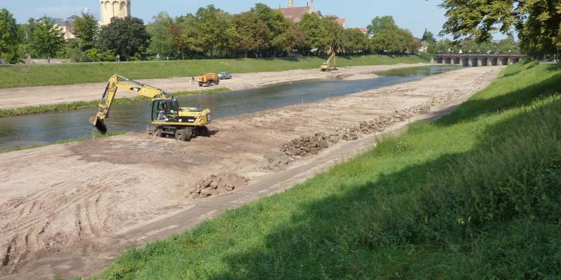 Foto: Ein Bagger entfernt Uferverbau an der Murg. Im Vordergrund sind Steine des Uferverbaus zu sehen, die rückverlagert wieder eingebaut wurden.